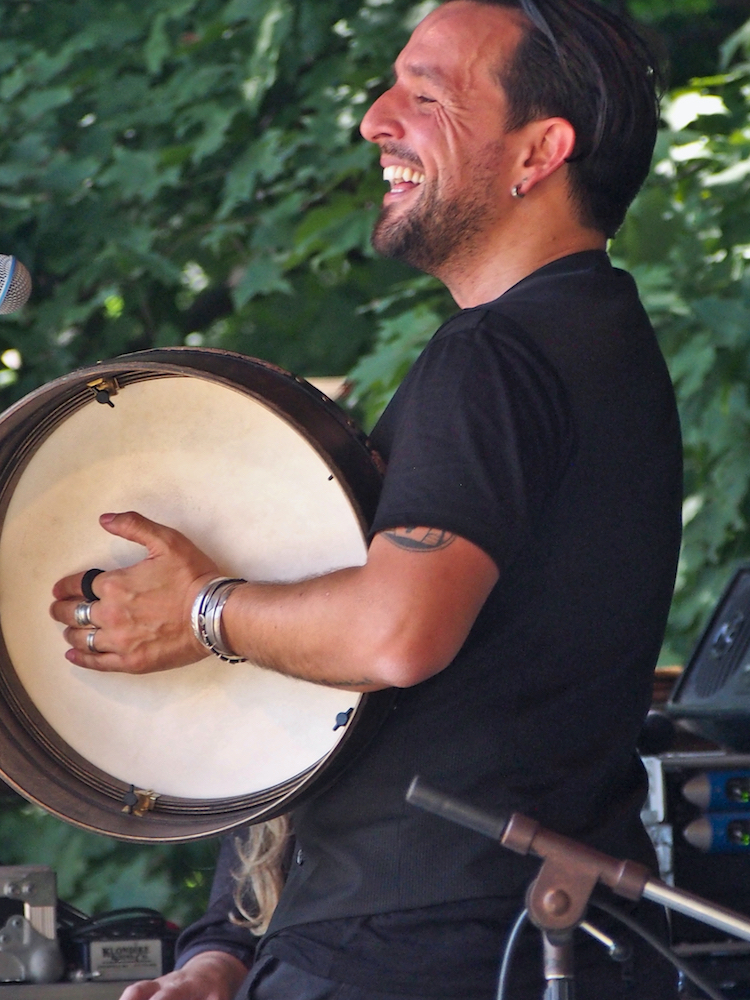 Andres Martorell of Baile An Salsa plays the bodhrán during the Celtic Workshop on the Camp Stage at the 56th annual Philadelphia Folk Festival (The High Note/ Shaun R. Smith).