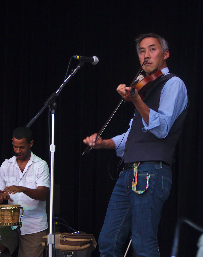 Members of Baile An Salsa, Michael Chang playing fiddle and Frailan Moran playing percussion, perform on the Martin Guitar Main Stage Sunday evening at the 56th annual Philadelphia Folk Festival (The High Note/ Shaun R. Smith).