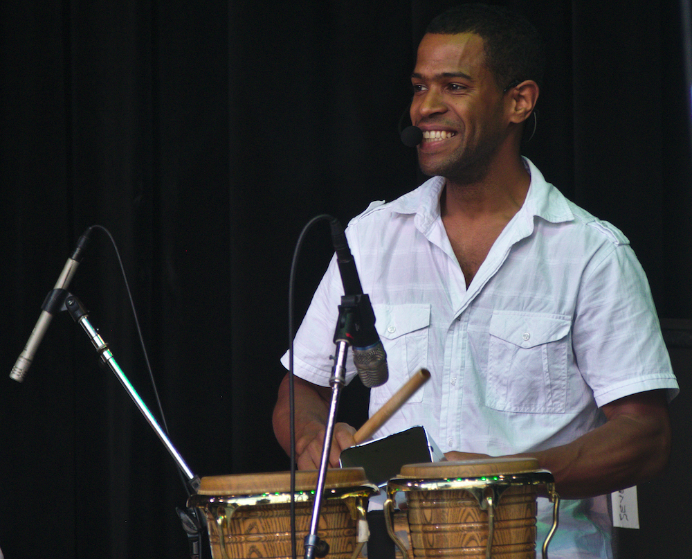 Frailan Moran of Baile An Salsa plays percussion on the Martin Guitar Main Stage Sunday evening at the 56th annual Philadelphia Folk Festival (The High Note/ Shaun R. Smith).